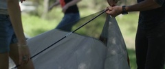 Three friends setting up a tent at campsite Stock Footage