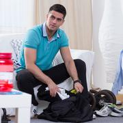 Man putting his sports equipment to the bag Stock Photos