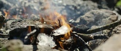Blazing campfire woods being arranged with shovel at campsite Stock Footage