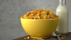 Cornflakes in yellow bowl with milk bottle in the background. Stock Footage