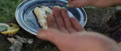 Person garnishing a cooked meal at campsite Stock Footage