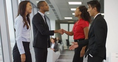 4k, Shot of a diverse group of coworkers shaking hands and talking in an office. Stock Footage