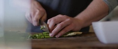 Man chopping vegetable on chopping board in the Kitchen Stock Footage