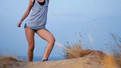 Beautiful blond girl dances on the beach at sunrise and birds on the background Stock Footage