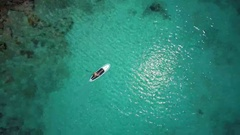 Aerial view of a bikini woman paddle boarding in tropical water, St John Stock Footage