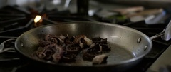 Person cooking octopus with fire on frying pan Stock Footage