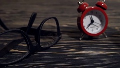 Glasses, mug and alarm clock on wooden background. Stock Footage