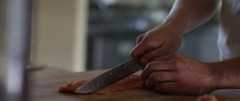 Man cutting meat with knife on wooden board Stock Footage