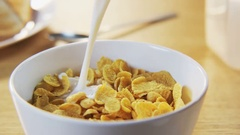 Pouring Milk into a Bowl with Corn Flakes Stock Footage