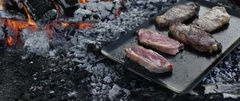 Steak being cooked on campfire at campsite Stock Footage