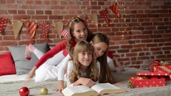 Triplets sisters dressed in xmas pajamas are playing on the bed, which is Stock Footage