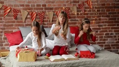 Three sisters dressed in xmas pajamas sitting on a decorated bed for the Stock Footage