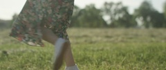 Happy woman in floral print dress dancing in the meadow Stock Footage