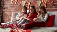 Three sisters sitting on the bed in xmas pajamas and eatting red apples Stock Footage