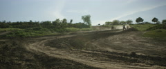 Motocross racers racing on winding road track in slow motion Stock Footage