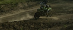 Motocross racer taking a turn while racing on a muddy road track in slow motion Stock Footage