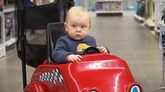 Baby sitting in the shopping cart in a store Stock Footage