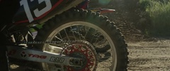 Motocross racers taking off on road track in slow motion Stock Footage
