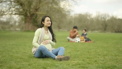 4K Portrait pregnant lady relaxing in the park with father & son in background Stock Footage