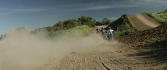Motocross racers racing on the muddy road track in slow motion Stock Footage