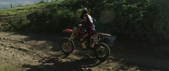 Motocross racers riding carefully on the stony road track in slow motion Stock Footage