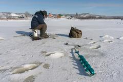 Winter fisherman on the river ice Stock Photos