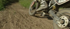 Motocross racer racing through the field in slow motion Stock Footage