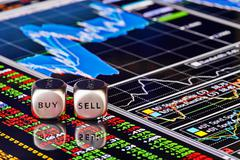 Dices cubes to trader. Cubes with the words SELL BUY on financial chart and c Stock Photos