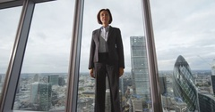 4K Portrait confident businesswoman standing by window in London city office Stock Footage