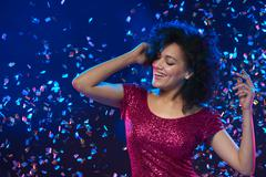 Woman dancing on a party over colorful background with confetti Kuvituskuvat