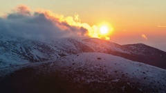 Sunset over snowy mountains time lapse. Frosty colorful evening clouds Stock Footage