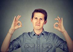 Satisfied man gesturing Ok sign Stock Photos