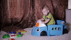 Baby child playing with a toy truck Stock Footage