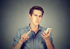 Man with cell phone showing no, don't, attention with finger gesture Stock Photos