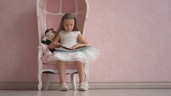 Pretty little girl with long hair in white dress sit on pink chair and reading Stock Footage
