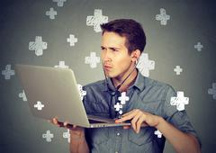Man listening computer with stethoscope looking at pc laptop. Stock Photos