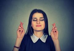 Hopeful beautiful woman crossing her fingers, eyes closed Stock Photos
