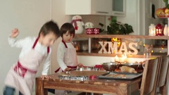 Two sweet children, boy brothers, preparing gingerbread cookies for Christmas Stock Footage