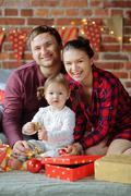Young family gleefully congratulates each other Marry Christmas. Stock Photos