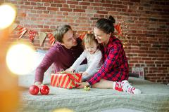 The daddy and mum give daughter the Christmas gift in bright packing Stock Photos