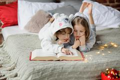 Children read a huge book of Christmas stories. Stock Photos