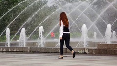 Young office worker walk against park fountain, enjoying fresh cool air Stock Footage