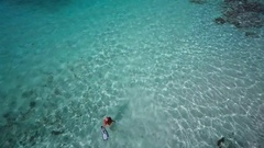 Aerial view of a bikini woman walking out to snorkel Stock Footage
