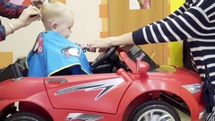 Little boy cuts the barber. He sits in a chair that looks like a car. Mom it Stock Footage