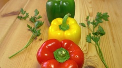 A person puts red, yellow and green paprika in the center of a wooden table Stock Footage
