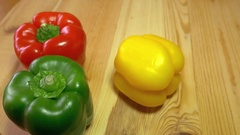 Red and green paprika lying on a wooden table and a yellow paprika rolls in Stock Footage