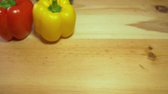 Three fresh paprika of different color lying on a wooden table, the shot moves Stock Footage