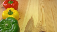 A chef lines up three paprika of different color on a wooden table Stock Footage