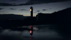 Lighthouse bokeh light flashes on the pier reflection in the late evening after Stock Footage