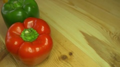 Three colorful paprika being rotated on a wooden table Stock Footage